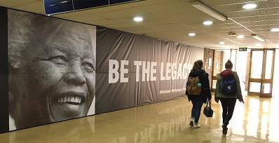 Students walk past the Nelson Mandela 100 memorial banner wall