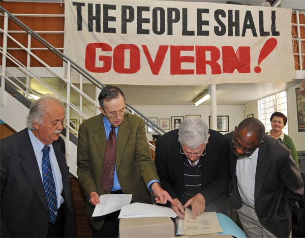 George Bizos, Joel Joffe, Arthur Chaskalson and Loyiso Nongxa view the original Rivonia Trial papers