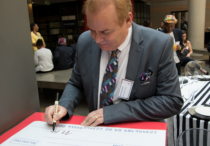 Gold Fields CEO Nick Holland signs the cheque.