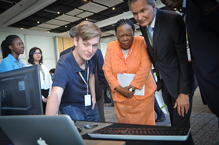 Physics student Matthew Spoor showing his work to Minister Naledi Pandor.