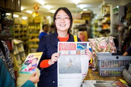 A visiting Chinese journalist in the Wits Africa China Reporting Project displays her story published in a Chinese newspaper in South Africa