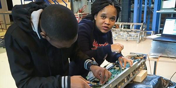 Students of the High Energy Particle Physics group works on a piece of electronic equipment