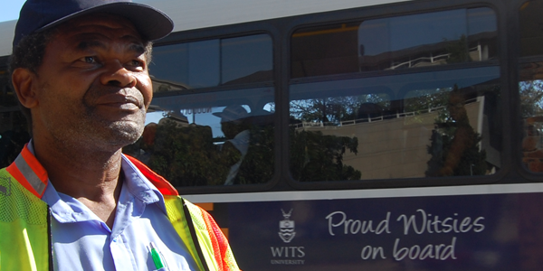 Parking attendant Michael Bodibe looks on as a Wits bus carrying students drives into campus.