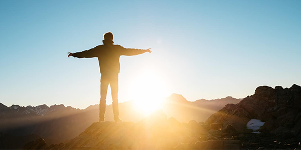 Man standing on with arms outstretched to sun