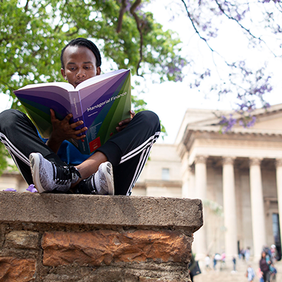 Student reading book with Great Hall in the background © Shivan Parusnath